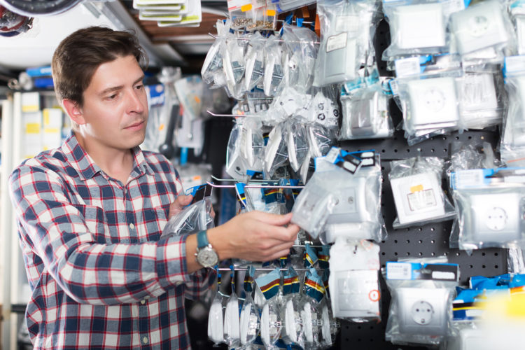 Portrait of adult positive male choosing electrical installation products